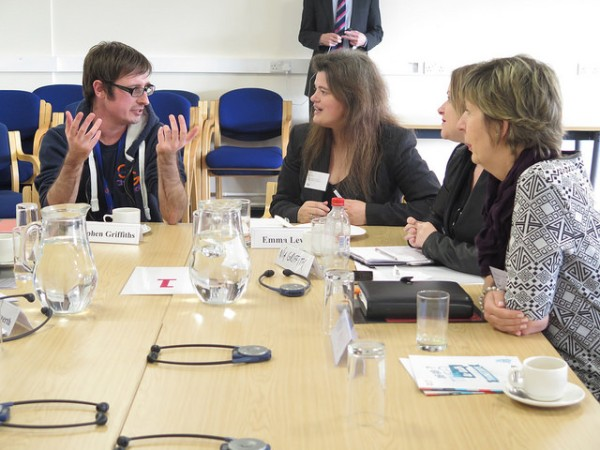 Four participants in discussion around a table at the workshop in Swansea.