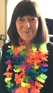 Photograph of Claire Clancy wearing a rainbow garland to prepare for Pride Cymru