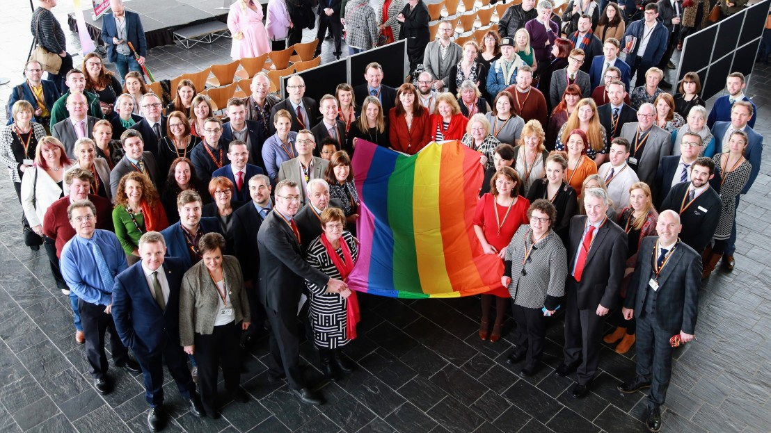 photo of LGBT staff and allies with the rainbow flag
